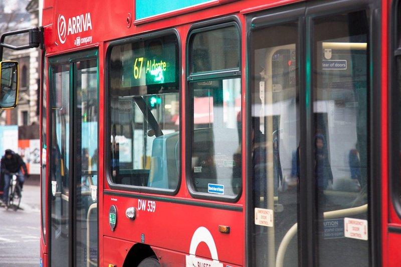 A close-up of the side of a red London bus heading towards Aldgate