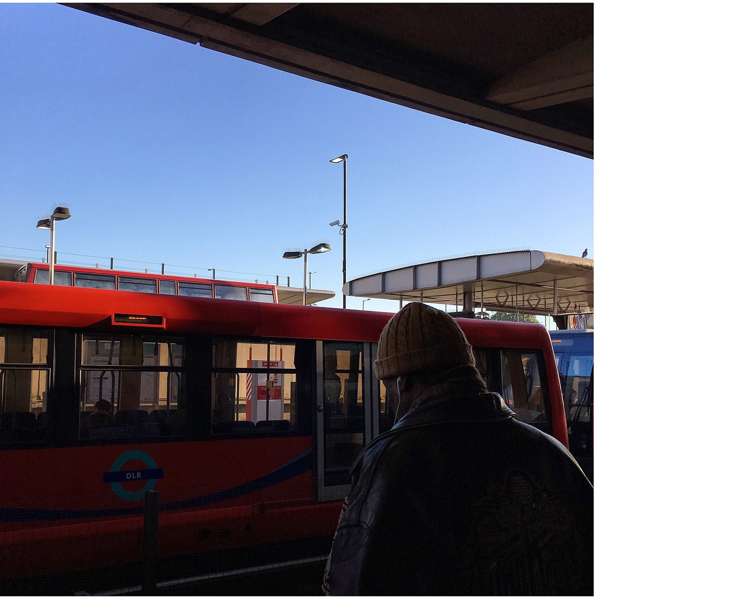 Man waiting for red DLR tube on sunny day with blue skies