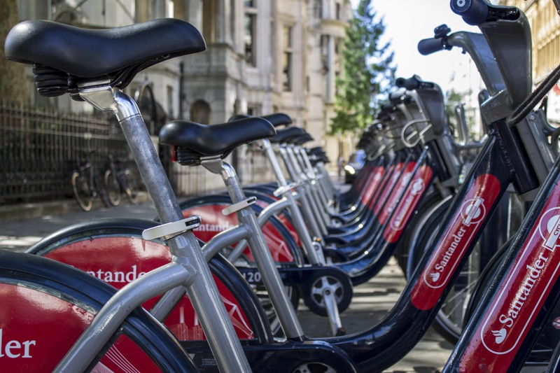A line of Santander bicycles motionless outside on a sunny day