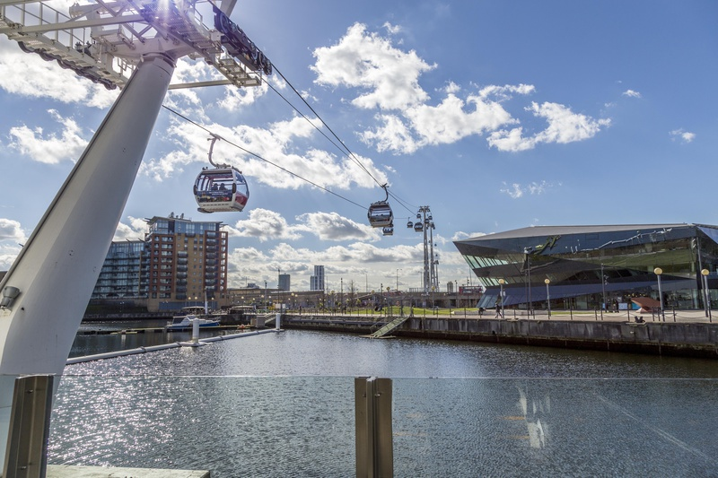 A shot of Emirates Cable Cars in motion taken from the ground, overlooking the water on a sunny day